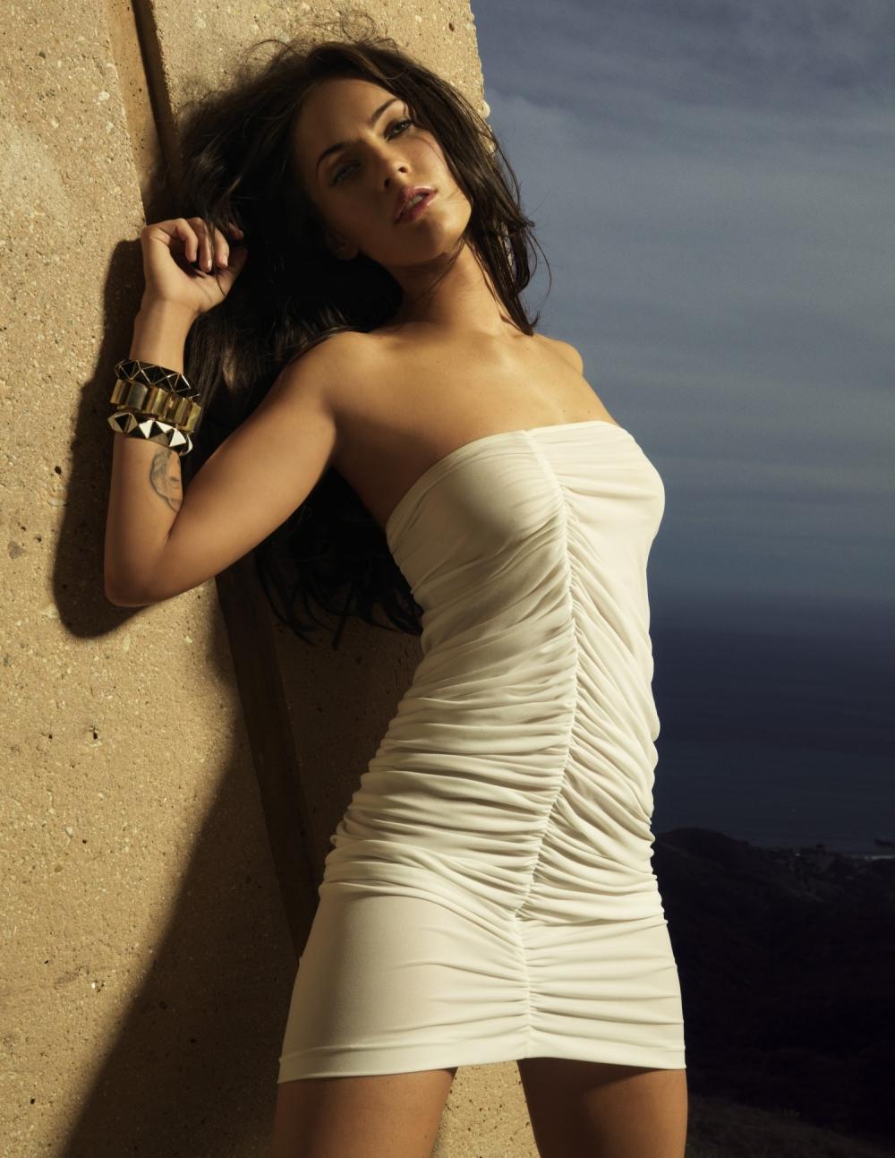 Меган Фокс в откровенном белом платье на фоне моря.